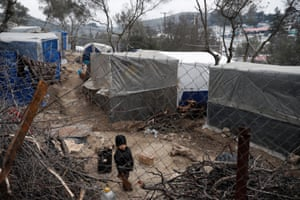 A refugee child stands in a makeshift camp next to the Moria refugee camp on Lesbos island.