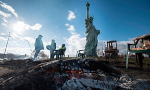 Protestors sit next to a replica of the Statue of Liberty in Colmar, eastern France