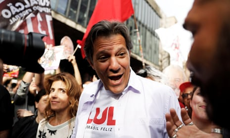 Fernando Haddad, with his wife Ana Estela, flashes the victory sign during a rally in São Paulo. One recent poll showed that more than a third of them have no idea who he is.