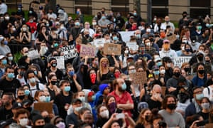 """Protestors hold up placards and raise their arms during a """"Black Lives Matter"""" demonstration over the death of George Floyd by a Minneapolis police officer, at Brooklyn Borough Hall on 1 June 2020 in New York."""