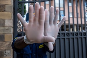 A guard shows the gloves that he hopes will protect him from the coronavirus