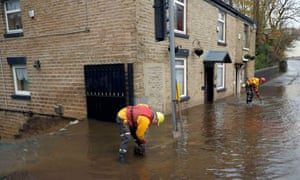 Emergency services workers try to clear floodwater in Stalybridge.
