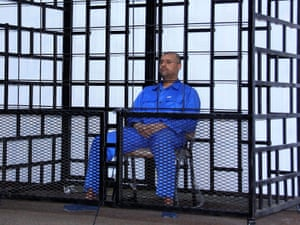 Saif Gaddafi attends a hearing behind bars in a courtroom in Zintan, May 2014.