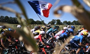 A man waves a French flag as the pack rides during the 11th stage between Chatelaillon Plage and Poitier.