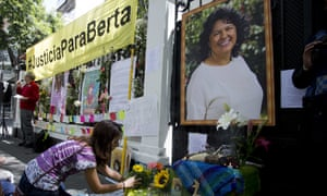 A woman places flowers on an altar set up in honor of Berta Cáceres during a demonstration outside Honduras' embassy in Mexico City on 15 June 2016.