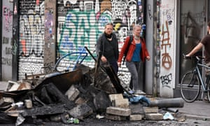 Residents in the Schanzenviertel district of Hamburg pass by a pile of burned debris following looting and rioting by G20 protesters.
