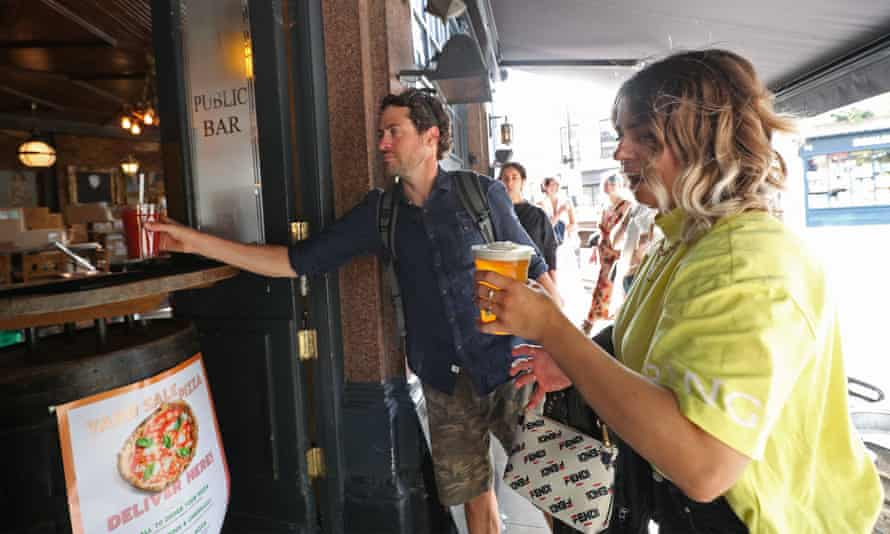 Customers served takeaway drinks in east London. Pubs and restaurants in England can reopen on 4 July in what the government calls a 'Covid-secure way'.