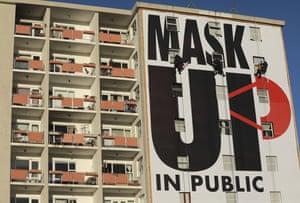 Papan iklan di gedung apartemen mendorong orang untuk memakai masker wajah di Cape Town.