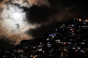 The rising supermoon over the slum of Petare in Caracas, Venezuela