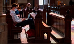 A student wearing a protective face mask studies on a computer as he sits on a pew at the Votive Church in Vienna,