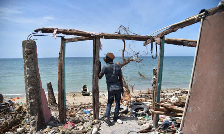 A man stands next to a destroyed house in Les Cayes, Haiti following Hurricane Matthew.