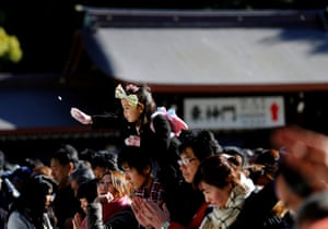 A girl throws a coin as she offers prayers at the Meiji Shrine in Tokyo, Japan.