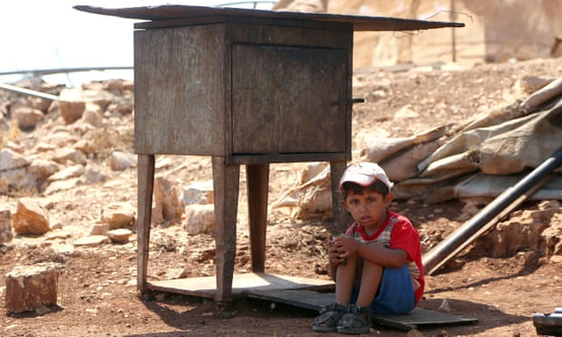 A Palestinian boy sits in the shade while his family search for their belongings after their shack near Ramallah was demolished by the Israeli army. More than 11,000 demolition orders are still outstanding.