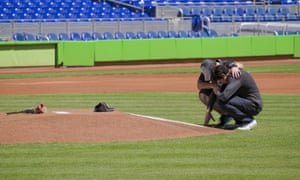 Miami Marlins' Christian Yelich, right, and team-mate Justin Bour kneel in front of a memorial on the pitcher's mound at Marlins Park for José Fernández