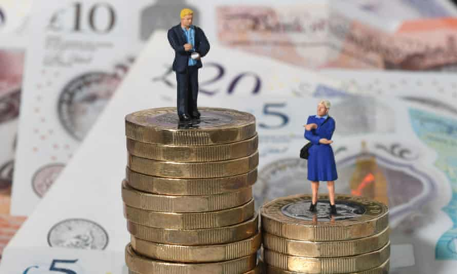 Models of a man and woman stand on a pile of coins and bank notes
