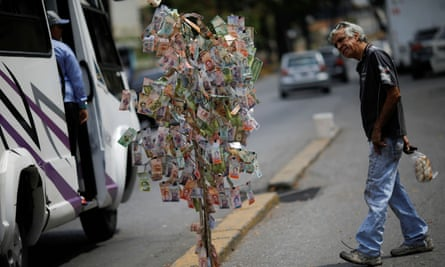 A man looks at Venezuelan bolívar notes hung to resemble a tree,in Caracas, Venezuela, on 6 March.
