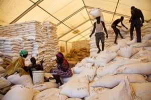 Men carry bags of food while women wait for their rations at the World Food Programme distribution site in Pibor, South Sudan.