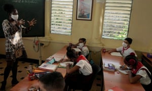 Children watch a lesson next to an image of late Cuban President Fidel Castro during their first day of classes since April amid COVID-19 concerns in Havana, Cuba.