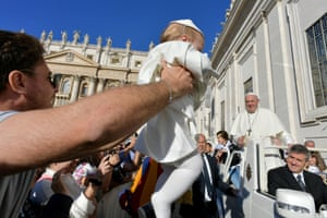 Rome, Italy. Pope Francis smiles at a baby dressed up as himself during his weekly general audience at the Vatican