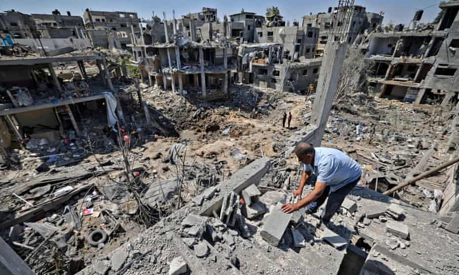 A Palestinian man standing in rubble assessing the damage caused by Israeli air strikes