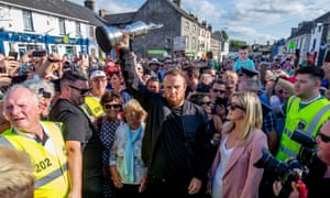 Shane Lowry is flanked by his grandmother Emily Scanlon and wife Wendy as he shows off the Claret Jug to the crowds