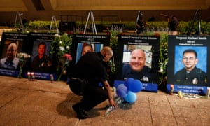 A Dallas police officer picks up balloons and flowers in front of images of the five officers killed.