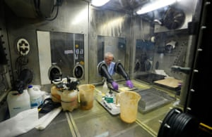 Randy Moss, a project chemist, works in an airtight chamber at the decontamination chamber
