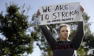 Rebecca Raede holds a sign reading 'We are T.O. Strong' across the street from the Thousand Oaks Teen Center, where relatives and friends gathered in the aftermath of the shooting.