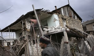 An ethnic Armenian man walks past a destroyed house in Nagorno-Karabakh in April.