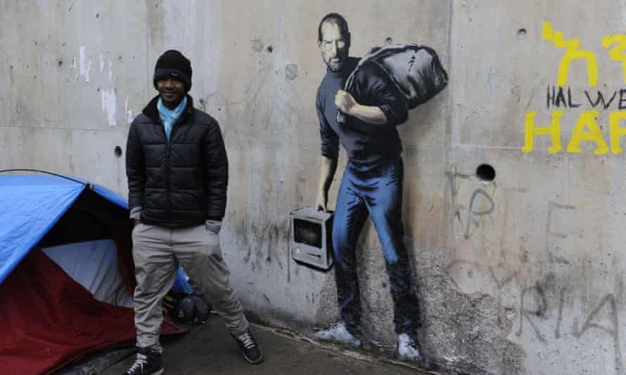 Banksy's graffiti portrait of Steve Jobs at the Jungle migrant camp, Calais, France: the artist offered disused materials from his Dismaland project to build shelters at the camp.