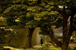 A salaryman stands at a pond in the Kyu Shiba Rikyu Garden in Tokyo, Japan.