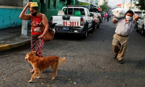 A woman walks with her dogs to cross a police checkpoint during a nationwide quarantine to prevent the spread of coronavirus in San Salvador, El Salvador 6 May 2020.