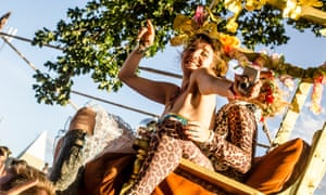Seated festival goers in fancy dress at The Secret Garden Party, Abbots Ripton, Huntingdon, Cambridgeshire.