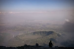 Volcanologists and rangers look down on the valley from the top of Nyiragongo