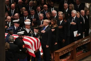 Donald Trump, Melania Trump, Barack Obama, Michelle Obama, and Bill Clinton salute the coffin of George HW Bush. Hillary Clinton and Jimmy Carter are to their left.