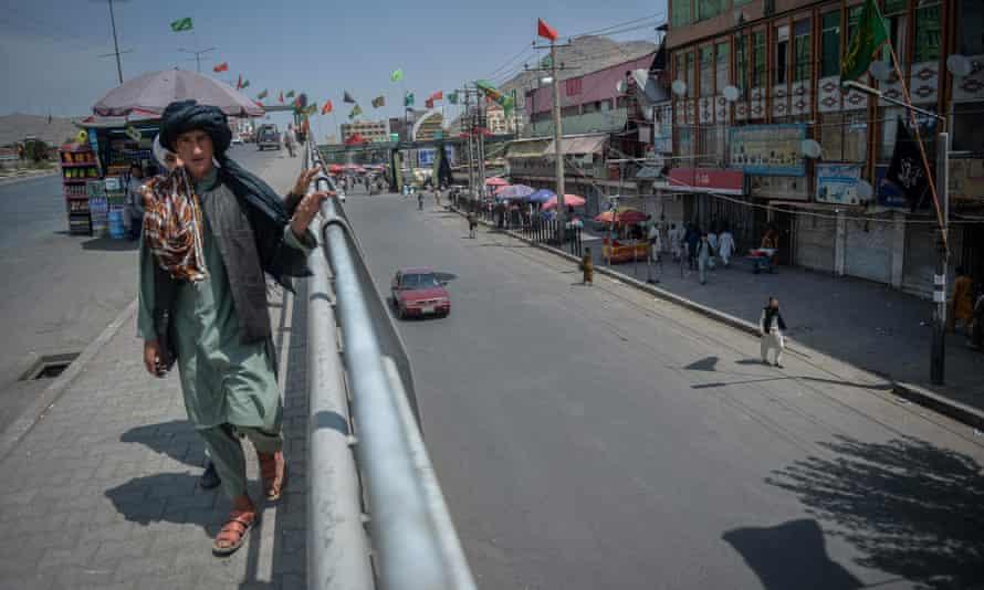 Afghan boy walks on bridge above empty road in Kabul