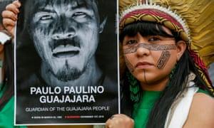 A woman wearing a traditional feathered headdress holding  a black and white image of Paulo Paulino Guajajara