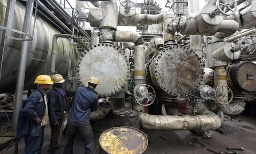 Workers trying to tie a pipe at an oil refinery in Nigeria