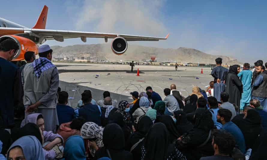 Afghan people sit on the tarmac as they hope to leave Kabul international airport on Monday