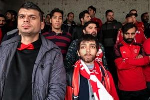 A woman watches a football match, disguised as a young man, in Tehran, Iran.