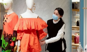 A woman wearing a protective face mask works in a Sydney retail store