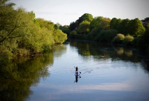 May 2020: a woman and her child enjoy the bank holiday sunshine as they paddleboard along the River Ouse