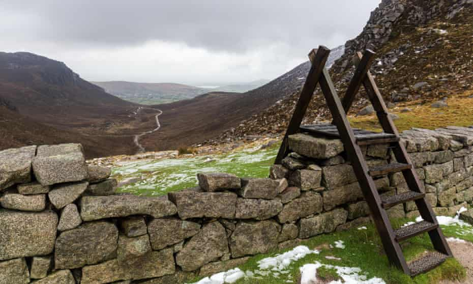 Wooden stile over the Mourne Wall at Hare's Gap with views down Trassey Track. Mourne Mountains, N.Ireland.PY7BHD Wooden stile over the Mourne Wall at Hare's Gap with views down Trassey Track. Mourne Mountains, N.Ireland.