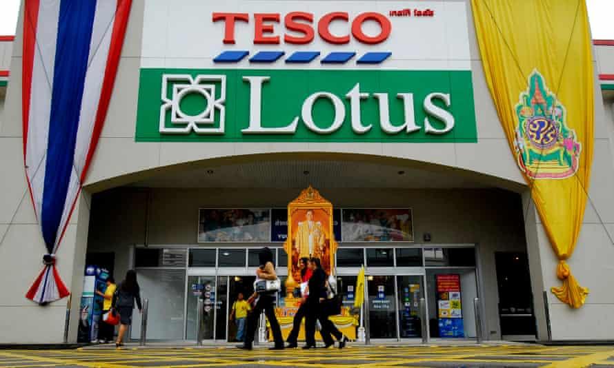 Shoppers pass a Tesco Lotus hypermarket in Bangkok, Thailand