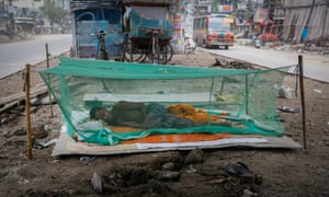 Bangladeshi worker sleeps under a mosquito net to avoid infection