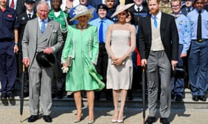 Prince Charles, Camilla, Duchess of Cornwall, Meghan, Duchess of Sussex, and Prince Harry, standing at the front of a crowd at Buckingham Palace