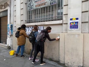 Camille, Natacha and Cindy glueing up posters in Paris demanding an end to femicides