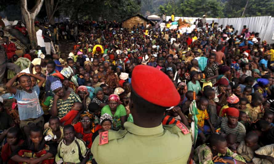 A Tanzanian policeman watches over Burundian refugees gathered on the shores of Lake Tanganyika in the Kigoma region.