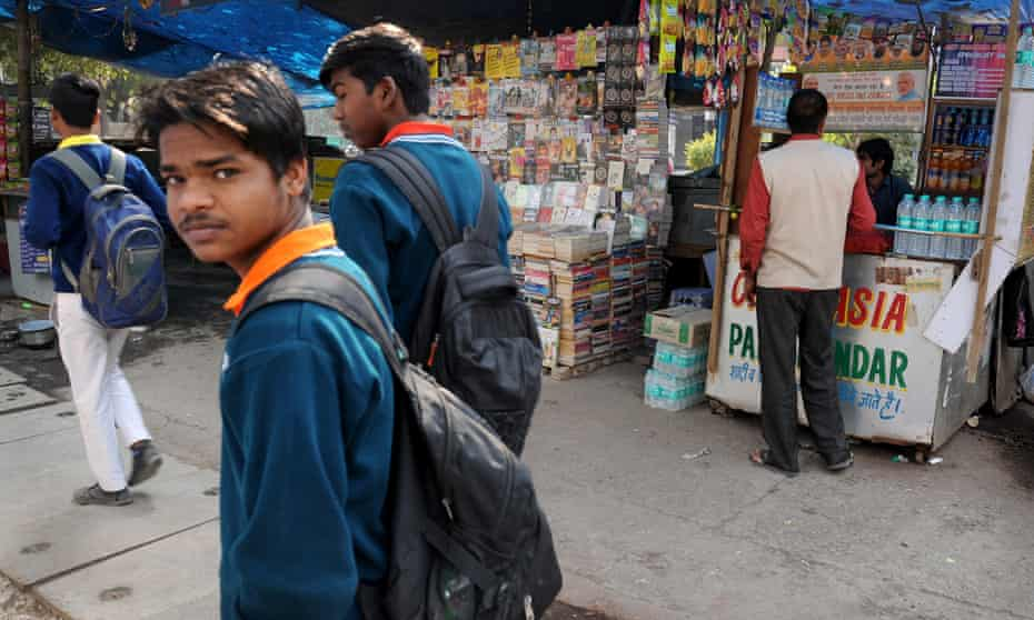 Students walked past a tobacco kiosk opposite the main gates of ASN Senior Secondary School in New Delhi, India.