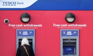 A customer uses a machine at a Tesco Bank cash point. Customers who lost money in the recent cyber attack have been refunded.
